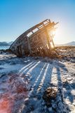 Northern Norway. Shipwrecked wooden viking boat on frozen beach in Northern Norway royalty free stock photography