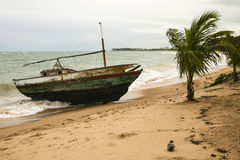 Shipwrecked, Worn Boat in a Storm. An old, worn, shipwrecked boat is stuck washed ashore as the gray clouds move in and the winds rise as evidenced by the Royalty Free Stock Image