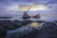 Shipwrecks. Ancient shipwrecks in the sea with sunset background Royalty Free Stock Photo