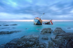 Shipwrecks. Ancient shipwrecks in the sea with sunset background Royalty Free Stock Photos