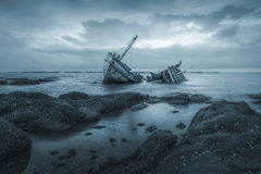 Shipwrecks. Ancient shipwrecks in the sea with sunset background blue color tone Royalty Free Stock Photo