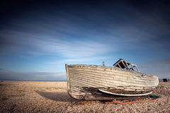 Shipwreckwd fishing boat stranded on pebbled beach. Dungeness, England Stock Image