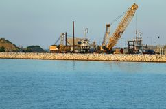 Shipyard for the construction of a sturdy dam with the crane. Shipyard for the construction of a robust dam with cranes and earth-moving machines Royalty Free Stock Photo