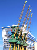 Shipyard cranes. With big cruise liner in the background stock images