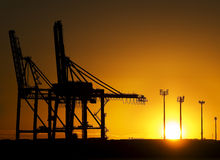Shipyard Cranes at Sunrise. The rising sun at Fisherman Islands Container Terminal in the Port of Brisbane, Queensland Australia, creates silhouettes of the Royalty Free Stock Photo