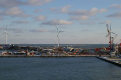 Shipyard at Frederokshavn, Denmark. Seaport and shipyard at Frederokshavn, Denmark with huge wind-powered electrical generators visible stock image