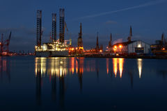 Shipyard at night. An industrial night scene of lights and tall cranes on the dockside reflected in  still water Stock Photo