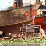 Shipyard number 2. Two men working at repairing an old ship with simple means on a shipyard in Bangladesh Royalty Free Stock Photo
