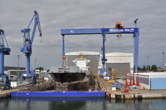 Shipyard in Rostock. Warnow shipyard in Rostock, Germany, with a dry dock with a ship inside and blue cranes Stock Photos