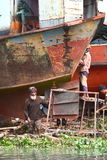 Shipyard. Two men working at repairing an old ship with simple means on a shipyard in Bangladesh Royalty Free Stock Photography