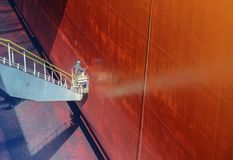 Wash and cleaning ship. Shipyard worker painting at the ship on the cherry picker royalty free stock photography