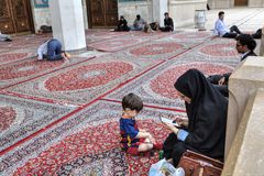Muslims rest and pray in courtyard of mosque, Shiraz, Iran. Shiraz, Iran - 19 april, 2017: Iranian Muslim woman, dressed in a chador with her child, a boy of Royalty Free Stock Image