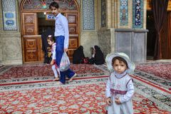 Little Iranian girl wearing beach cap stands in mosque courtyard Royalty Free Stock Photography