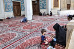 Islamic woman with child is sitting in courtyard of mosque. Shiraz, Iran - 19 april, 2017: A young Muslim woman in an Islamic veil looks through information on Royalty Free Stock Images