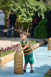 Iranian boy playing with fountain in Eram Garden in Shiraz. Iran. Shiraz, Iran - March 25, 2018: Iranian boy playing with fountain in Eram Garden is historic royalty free stock photography