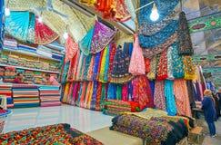 Colorful fabrics in stall of Vakil Bazaar, Shiraz, Iran. SHIRAZ, IRAN - OCTOBER 14, 2017: Interior of a stall in Vakil Bazaar with many colorful fabrics of silk royalty free stock photography