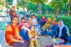 Persian family on picnic, Shiraz, Iran. SHIRAZ, IRAN - OCTOBER 13, 2017: Large Iranian family with kids on traditional Friday picnic in Hafezieh public park, on royalty free stock photos