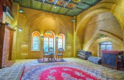 Carpet gallery in Shiraz, Iran. SHIRAZ, IRAN - OCTOBER 14, 2017: The medieval hall of carpet market with relief brick walls, ornate ceiling, stained-glass royalty free stock photography