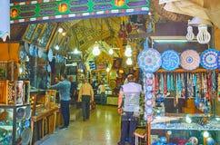 Interior of Saraye Moshir Bazaar, Shiraz, Iran. SHIRAZ, IRAN - OCTOBER 14, 2017: The narrow vaulted alleyway with many small stalls of Saraye Moshir Bazaar royalty free stock photos