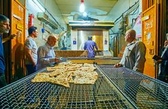 SHIRAZ, IRAN - OCTOBER 13, 2017: The old bakery offers the fresh tasty flatbread, in evening there are always many clients, buying. Just baked hot bread, on stock images