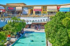 The garden of Saraye Moshir Bazaar, Shiraz, Iran. SHIRAZ, IRAN - OCTOBER 14, 2017: The scenic area of Saraye Moshir Bazaar with fountain in the middle, shady royalty free stock photo