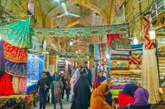 Walk through textile section of Vakil Bazaar, Shiraz, Iran. SHIRAZ, IRAN - OCTOBER 14, 2017: Textile section of Vakil Bazaar with many colorful fabrics in stalls stock image