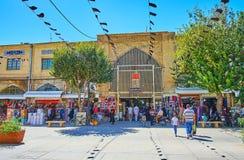 Zand street with black Ashura flags, Shiraz, Iran. SHIRAZ, IRAN - OCTOBER 14, 2017: The urban scene in Zand walking street with a view on the portal of stock photo