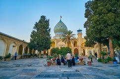 SHIRAZ IRAN - OKTOBER 12, 2017: Besökarna av Imamzadeh Ali Ibn Hamzeh Holy Shrine kopplar av på dess sceniska trädgård som in lok royaltyfria foton