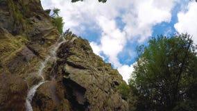 Shirlak-Wasserfall in den Felsen auf blauem Himmel mit Weiß bewölkt Hintergrund Zeitspanne 4K, Altai-Berge stock footage
