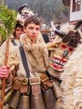 SHIROKA LAKA, BULGARIEN - mars 6, 2011: Den unga pojken deltar i den Kukeri festivalen Presponedelnik arkivfoton