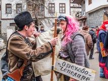 SHIROKA LAKA, BULGARIJE - Maart 6, 2011: Bagpiper en een geklede mens hebben pret bij het Kukeri-festival Presponedelnik royalty-vrije stock foto's