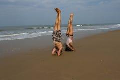 Shirshasana. A man and a woman are practicing yoga on the shores of a warm sea. India, Karnataka, Gokarna. March, 2017 Stock Images