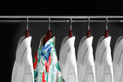 Shirt. Tropical shirt between white shirts hanging inside a closet Royalty Free Stock Images