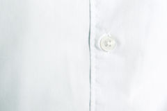 Shirt button detail. White cotton fabric. Royalty Free Stock Photo