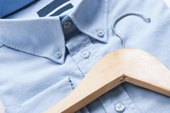 Shirt and cloth hanger. Wooden cloth hanger on top of blue shirt Stock Photo