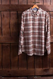 Shirt of cowboy. Fitting room in a clothing store. Checkered shirt is hanging on a wooden fence. Shirt of cowboy Stock Photos