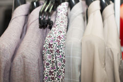 Shirt with flower print and jackets beige hue on a hanger in the store.  Stock Photo