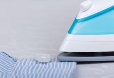 Shirt ironing using  steam iron on  light gray background. Stock Photo