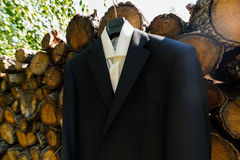 The shirt and jacket of the groom hang on a clothes hanger. Next to a stack Royalty Free Stock Photo
