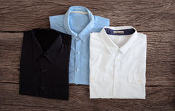 Shirt and Jeans shirt on wooden background Royalty Free Stock Images