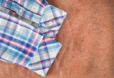 Shirt sleeves. Tartan patterned shirt sleeves on a leather background Royalty Free Stock Photo