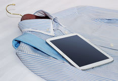 Shirt and a tablet on the bed Stock Photography