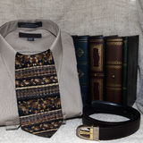 Shirt and Tie. Folded shirt with tie and belt and books in the background Royalty Free Stock Photo