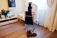 Shirt with trousers on a hanger with shoes and men`s accessories. Set of groom clothes on wedding day Stock Photography