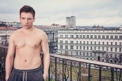 Shirtles knappe jonge mens in sweatpants die zich op terras bevinden royalty-vrije stock afbeeldingen