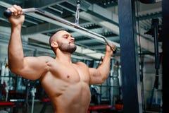 Shirtless öva för kroppsbyggare Ung idrottsman nenman på armpressmaskinen på en idrottshallbakgrund Muskelbyggnadsbegrepp Royaltyfri Bild