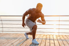 Shirtless african man athlete warming up and training on pier Stock Photos