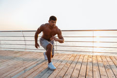Shirtless african young sportsman working out on pier Royalty Free Stock Photos