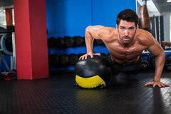 Shirtless athlete doing push-ups with exercise ball Royalty Free Stock Photos