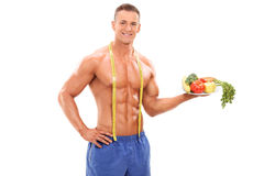 Shirtless athlete holding a plate with vegetables royalty free stock photo